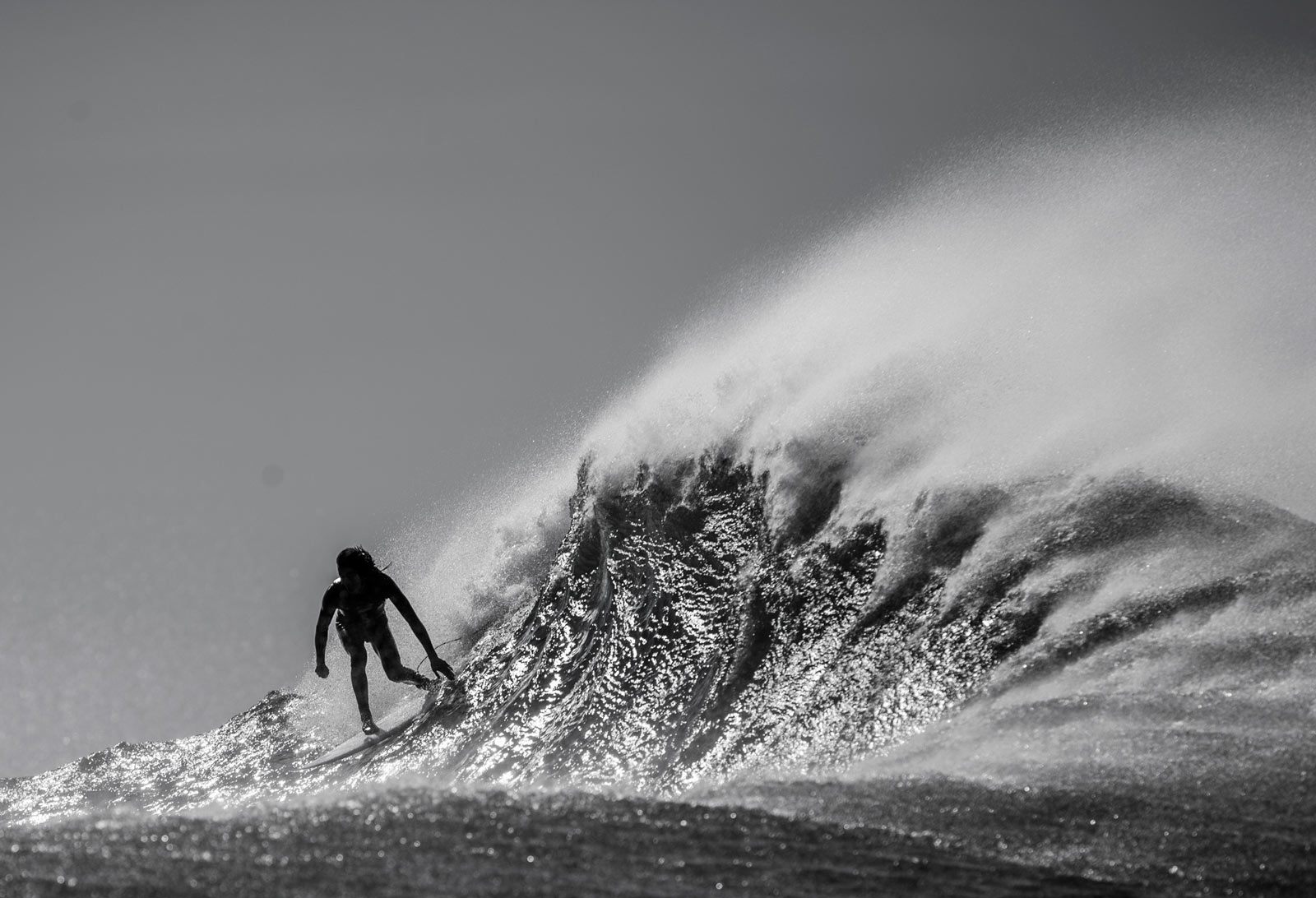 Black and White photo of Craig Anderson surifng a late afternoon wave